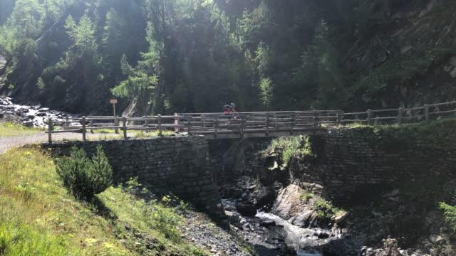Aerial drone view of a mountain biker on a bridge singletrack trail. - Slow Motion