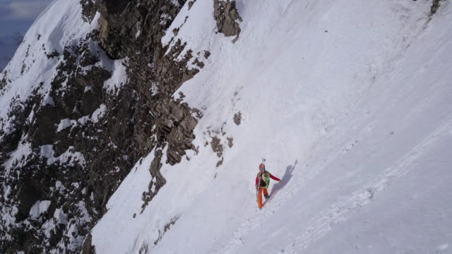 Aerial drone view of a mountain climber climbing up with crampons in the snow.