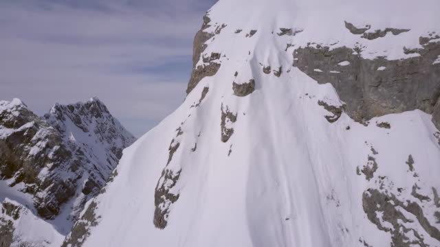 aerial drone view of a mountain climber skier on the peak summit top of a snow covered mountain. - mont blanc stock videos & royalty-free footage