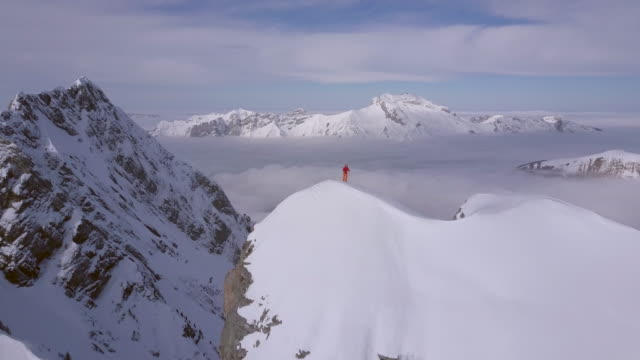 Aerial drone view of a mountain climber skier on the peak summit top of a snow covered mountain.