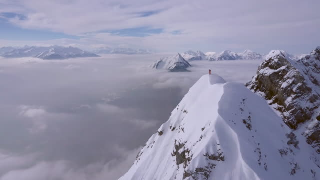 vidéos et rushes de aerial drone view of a mountain climber skier on the peak summit top of a snow covered mountain. - sommet montagne