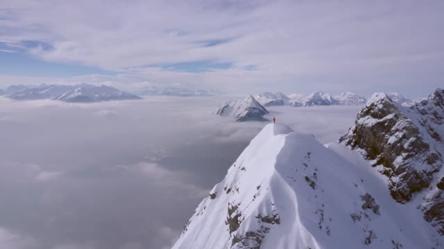 aerial drone view of a mountain climber skier on the peak summit top of a snow covered mountain. - alpi video stock e b–roll