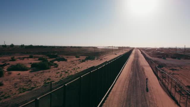 西テキサスからニューメキシコまで広がる狭い孤独な砂漠の高速道路の空中ドローンビュー - 囲み塀点の映像素材/bロール