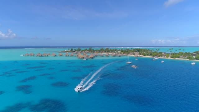 vidéos et rushes de aerial drone view of a pier dock and boat at a luxury resort and overwater bungalows in bora bora tropical island. - bora bora