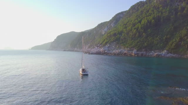 aerial drone view of a sailboat anchored in a bay below mamma mia cliff in skopelos island, greece. - mediterranean culture stock videos & royalty-free footage