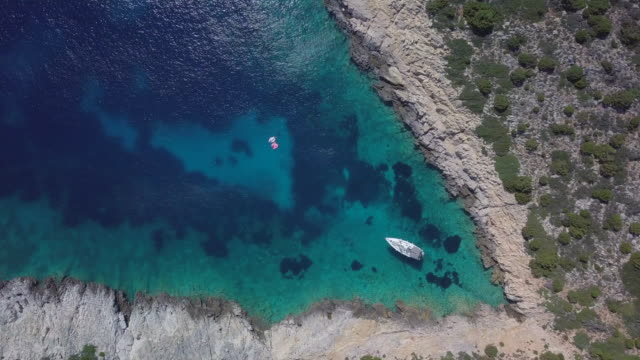 aerial drone view of a sailboat anchored in a v shaped bay in skiathos, greece. - time-lapse - anchored stock videos & royalty-free footage