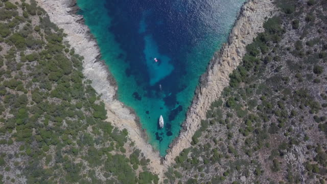 aerial drone view of a sailboat anchored in a v shaped bay in skiathos, greece. - time-lapse - zen like stock videos & royalty-free footage