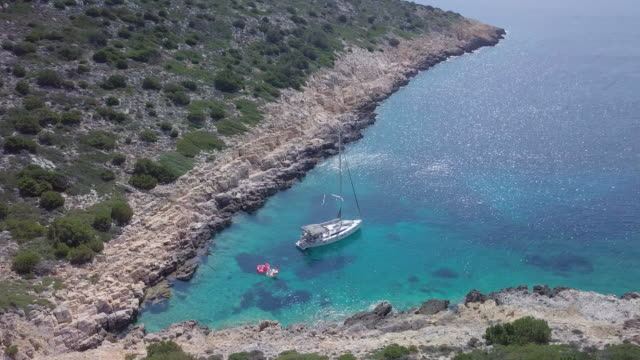 aerial drone view of a sailboat anchored in a v shaped bay in skiathos, greece. - anchored stock videos & royalty-free footage