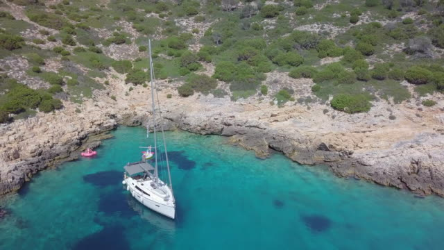 aerial drone view of a sailboat anchored in a v shaped bay in skiathos, greece. - mediterranean culture stock videos & royalty-free footage