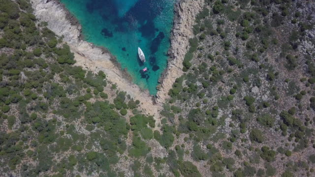 aerial drone view of a sailboat anchored in a v shaped bay in skiathos, greece. - shape stock videos & royalty-free footage