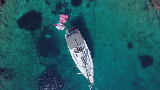 aerial drone view of a sailboat anchored in a v shaped bay in skiathos, greece. - griechenland stock-videos und b-roll-filmmaterial