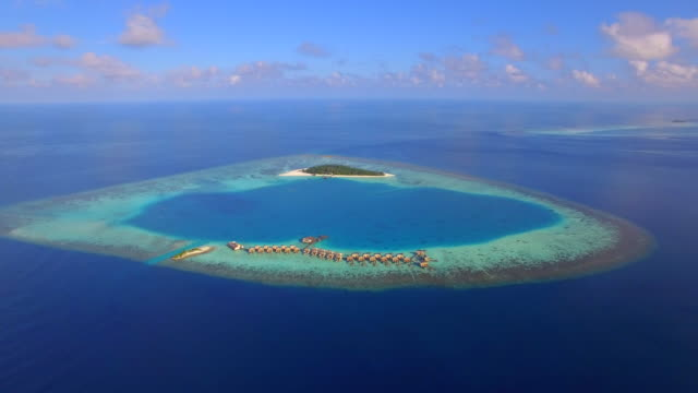 aerial drone view of a scenic tropical island and resort hotel with overwater bungalows in the maldives. - unbelievable stock videos and b-roll footage