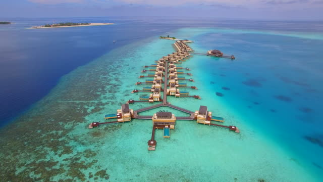 Aerial drone view of a scenic tropical island and resort hotel with overwater bungalows in the Maldives.
