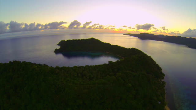 vídeos de stock, filmes e b-roll de aerial drone view of a scenic tropical island in fiji at sunset. - atol