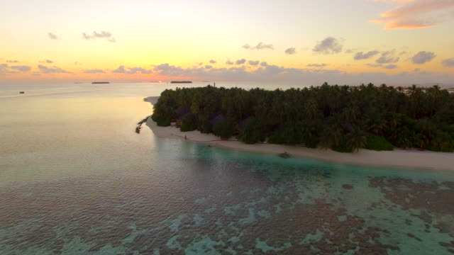 Aerial drone view of a scenic tropical island in the Maldives at sunset.