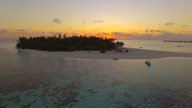 aerial drone view of a scenic tropical island in the maldives at sunset. - island stock videos and b-roll footage