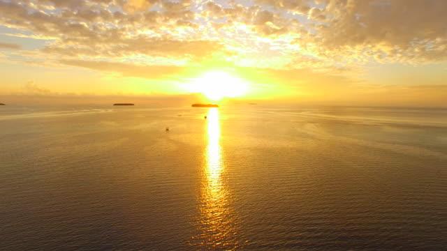 vidéos et rushes de aerial drone view of a scenic tropical island in the maldives at sunset. - partie d'une série