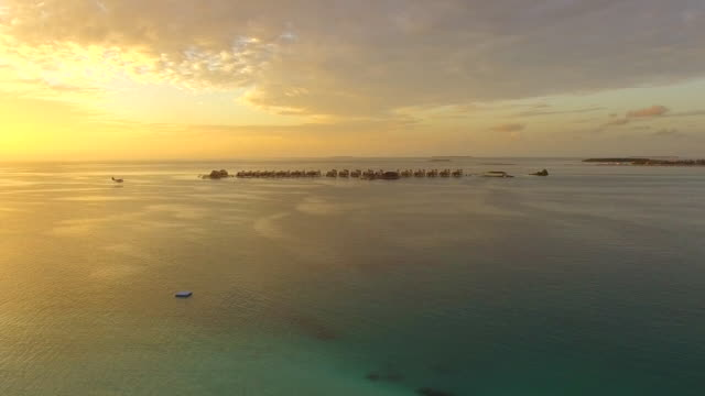 Aerial drone view of a seaplane landing at a tropical island in the Maldives.