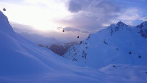 vídeos de stock, filmes e b-roll de aerial drone view of a ski gondola lift and mountains at a ski resort. - teleférico veículo terrestre comercial