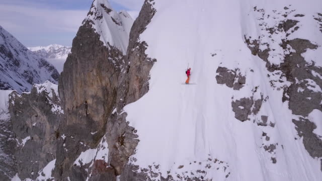 Aerial drone view of a skier skiing down a steep snow covered mountain.