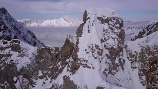 aerial drone view of a skier skiing down a steep snow covered mountain. - alpi video stock e b–roll
