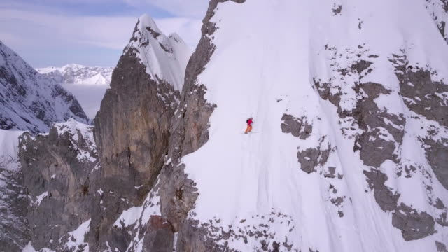 Aerial drone view of a skier skiing down a steep snow covered mountain. - Time-Lapse