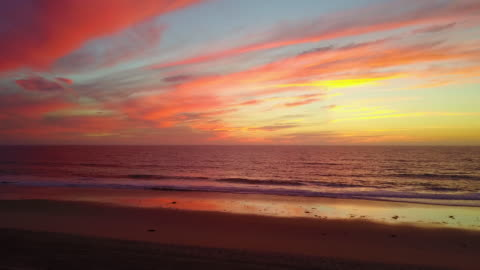 aerial drone view of a sunset at the beach over the ocean. - sunset stock videos & royalty-free footage