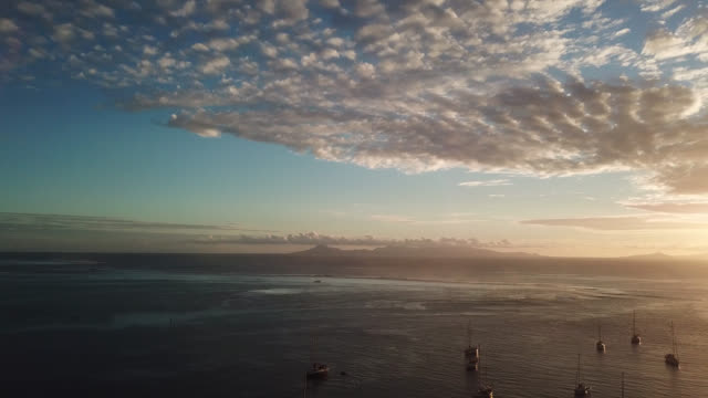stockvideo's en b-roll-footage met aerial drone view  of a sunset on the sea with sailboats, moutain - huahine