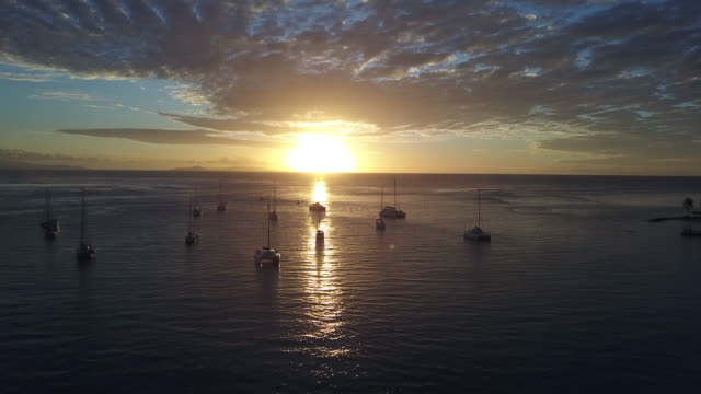 stockvideo's en b-roll-footage met aerial drone view  of a sunset on the sea with sailboats - huahine
