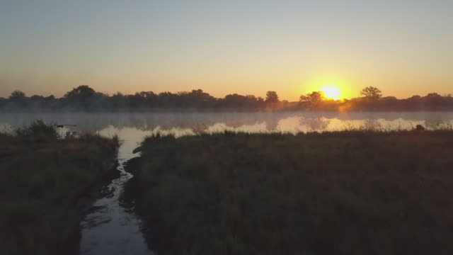 aerial drone view of a sunset sunrise over a lake with fog in africa. - ボツワナ点の映像素材/bロール
