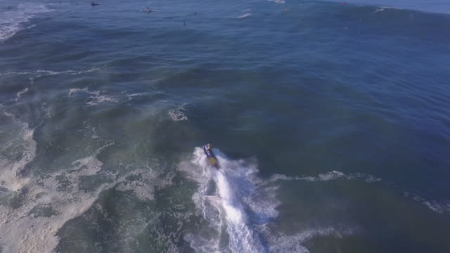 Aerial drone view of a surfer being rescued by lifeguards on a personal watercraft jetski waverunner while surfing waves.