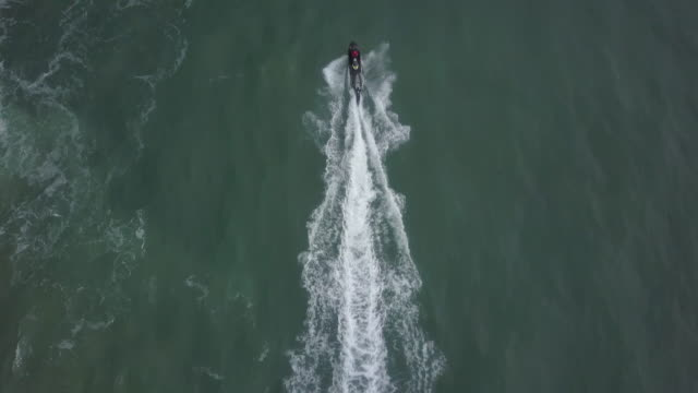 aerial drone view of a surfer being rescued by lifeguards on a personal watercraft jetski waverunner while surfing waves. - jet ski stock videos & royalty-free footage
