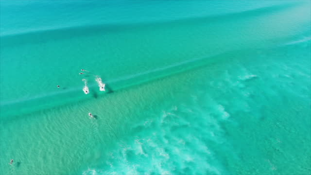 aerial drone view of a surfer surfing waves on his surfboard. - slow motion - risk stock videos & royalty-free footage