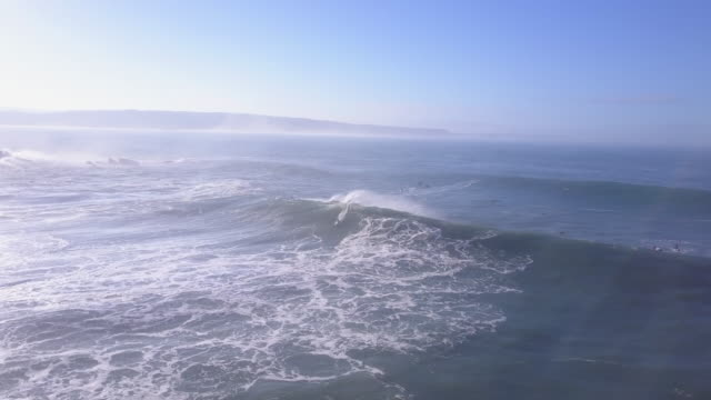 Aerial drone view of a surfer surfing waves on his surfboard.