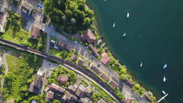 vídeos de stock e filmes b-roll de aerial drone view of a town with train tracks near lake maggiore, switzerland. - switzerland