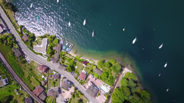 aerial drone view of a town with train tracks near lake maggiore, switzerland. - ticino canton stock videos and b-roll footage