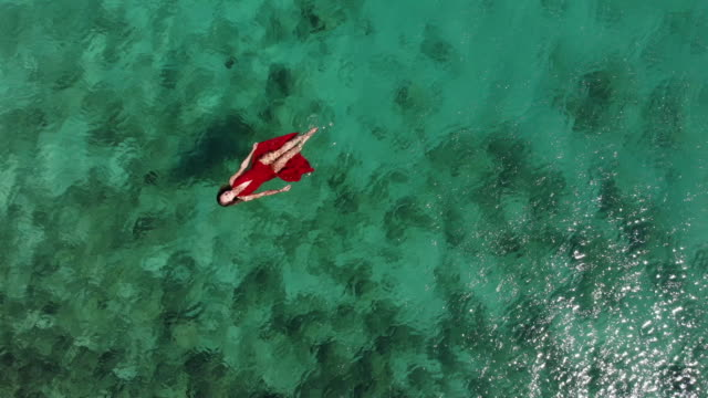 aerial drone view of a woman floating and swimming on a tropical sea - fashion video stock e b–roll