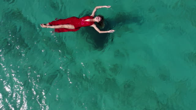aerial drone view of a woman floating and swimming on a tropical sea - standing water stock videos & royalty-free footage