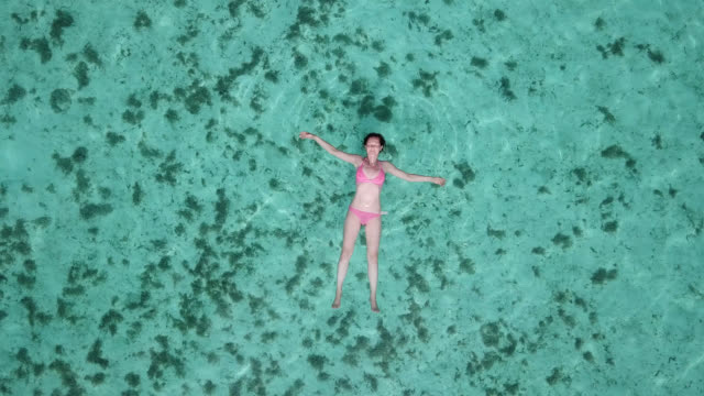aerial drone view of a woman  floating and swimming on a tropical island. - floating on water stock videos & royalty-free footage