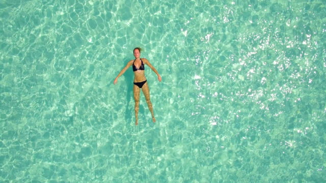 aerial drone view of a woman floating and swimming on a tropical island. - galleggiare sull'acqua video stock e b–roll
