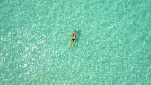 aerial drone view of a woman floating and swimming on a tropical island. - reinheit stock-videos und b-roll-filmmaterial