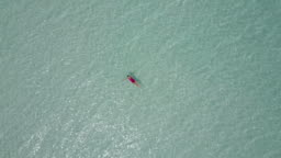 Aerial Drone View of a Woman Floating and Swimming on Bacalar Lagoon, Mexico.