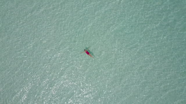 aerial drone view of a woman floating and swimming on bacalar lagoon, mexico. - galleggiare sull'acqua video stock e b–roll