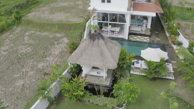 vidéos et rushes de aerial drone view of a woman getting a massage at a villa resort hotel while traveling. - massage room