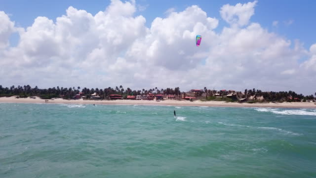 Aerial drone view of a woman kiteboarding on a kite board.