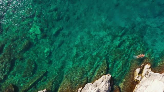 風光明媚なバレアレス諸島の周りを泳ぐ女性の空中ドローンビュー。 - バレアレス点の映像素材/bロール