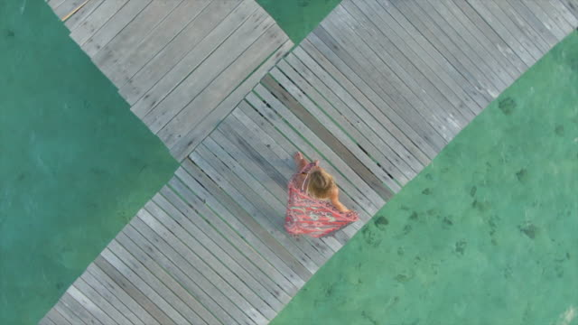 vidéos et rushes de aerial drone view of a woman spinning with a sarong on a deck at tropical island in over water bungalow hotel resort. - lagon