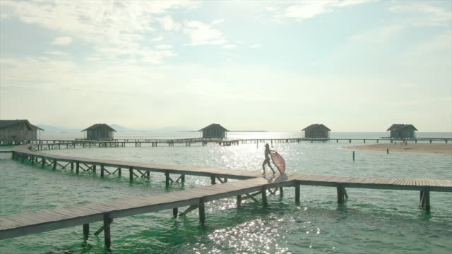 vidéos et rushes de aerial drone view of a woman spinning with a sarong on a deck at tropical island in over water bungalow hotel resort. - sarong