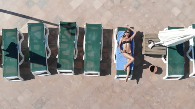aerial drone view of a woman sunbathing next to swimming pool - next to stock videos and b-roll footage
