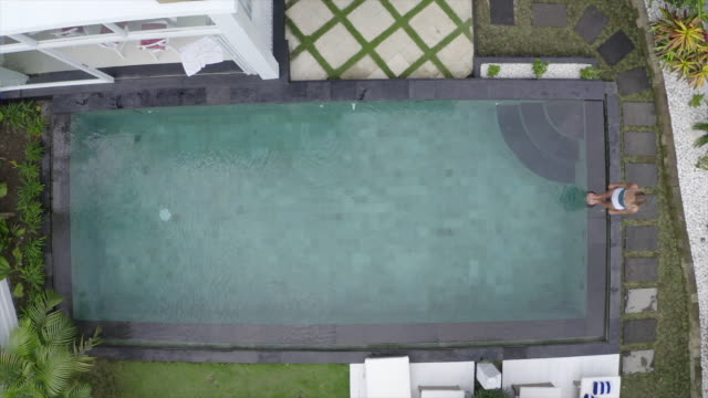 aerial drone view of a woman swimming in a pool at a villa resort hotel traveling in exotic tropical bali, indonesia. - freibad stock-videos und b-roll-filmmaterial